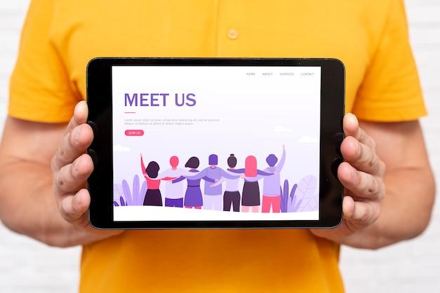 Rencontrez-nous page de destination sur tablette tenue par l'homme Psd gratuit