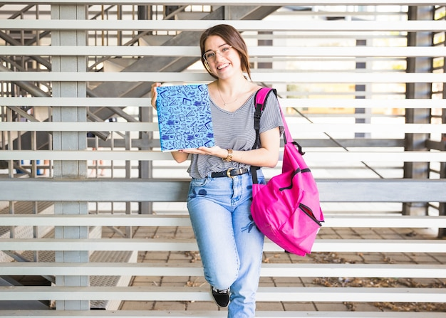 Retour à la notion d'école avec une fille présentant une couverture de livre Psd gratuit