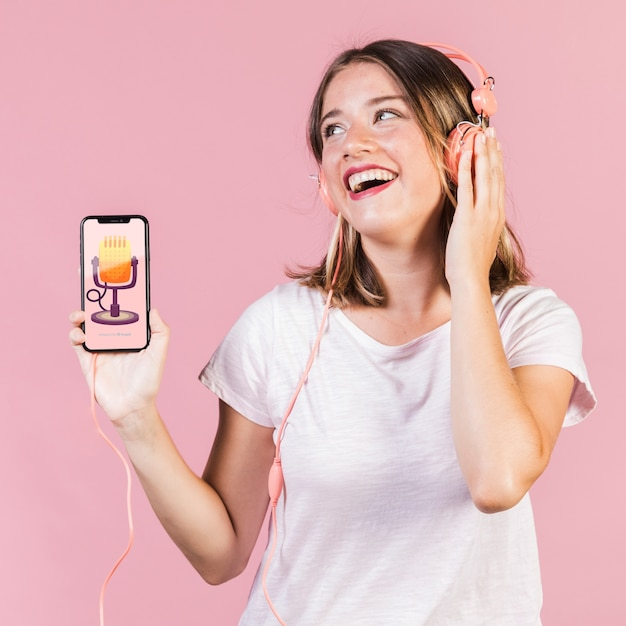 Rire jeune femme avec un casque tenant une maquette de téléphone portable Psd gratuit