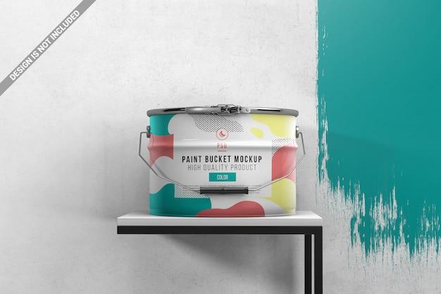 Seau de peinture sur table avec mur peint PSD Premium