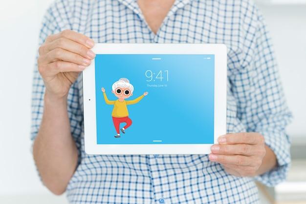 Senior femme tenant une maquette de tablette Psd gratuit