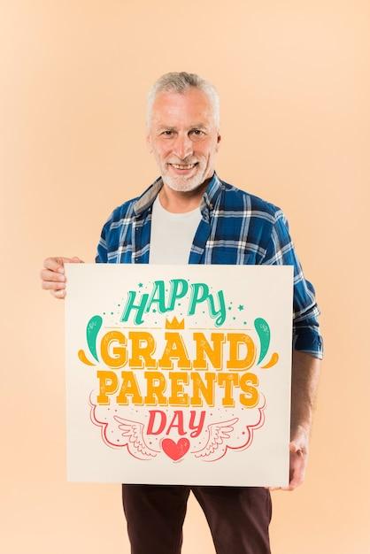 Senior homme présentant le tableau pour la journée des grands-parents Psd gratuit