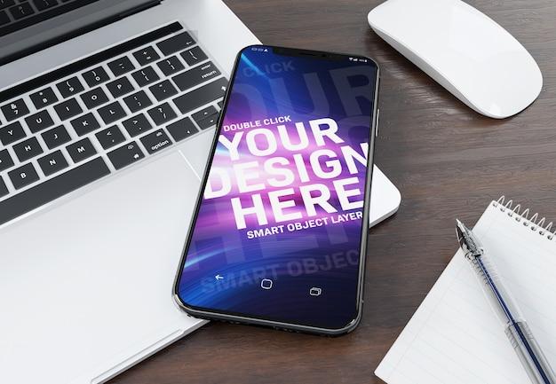 Smartphone moderne portant sur une maquette d'ordinateur portable PSD Premium
