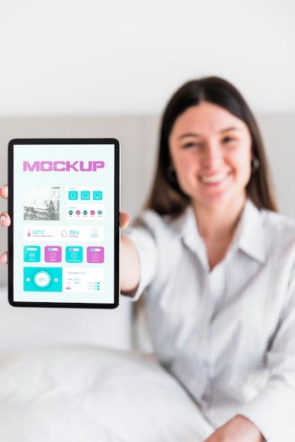 Smiley Woman Holding Tablet Avec Maquette Psd gratuit