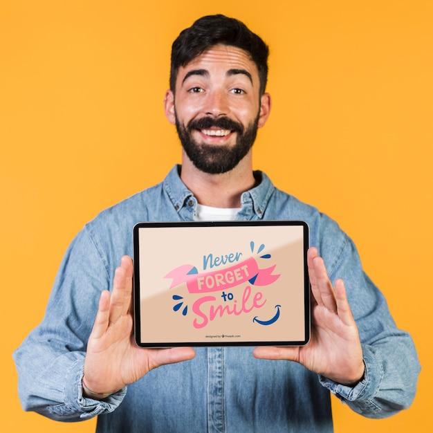 Souriant homme barbu présentant une tablette maquette Psd gratuit