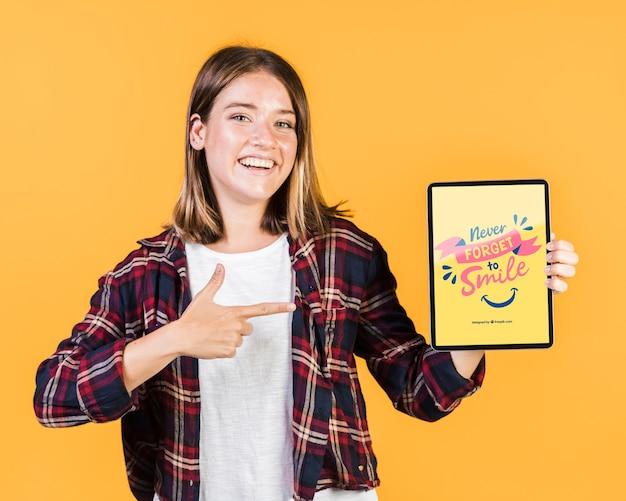 Souriant jeune femme pointant le doigt sur une maquette de tablette Psd gratuit