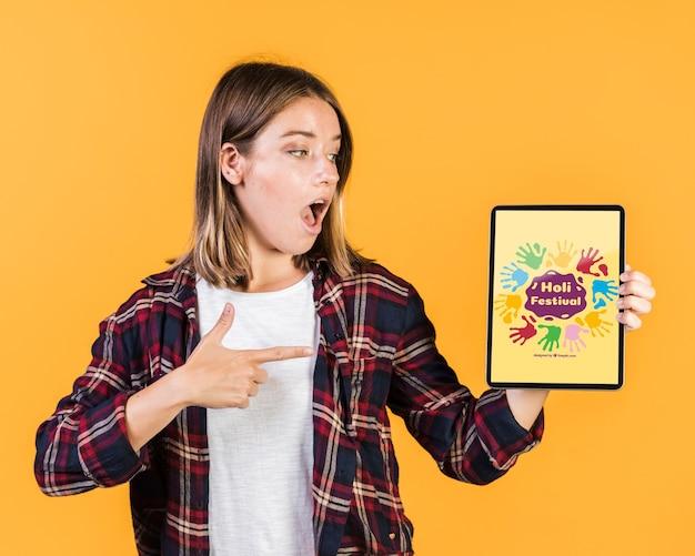 Surpris jeune femme montrant un doigt pointé sur une maquette de tablette Psd gratuit