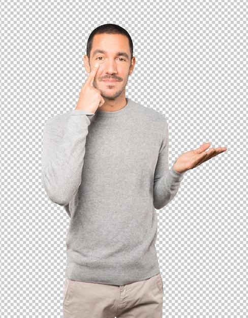 Sympathique Jeune Homme Faisant Un Geste D'être Prudent Avec Sa Main Pointant Vers Son œil PSD Premium