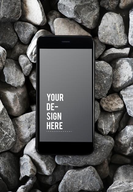 Téléphone portable sur une surface rocheuse Psd gratuit