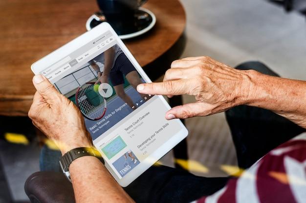 Vieil homme regardant les nouvelles sur une tablette numérique PSD Premium