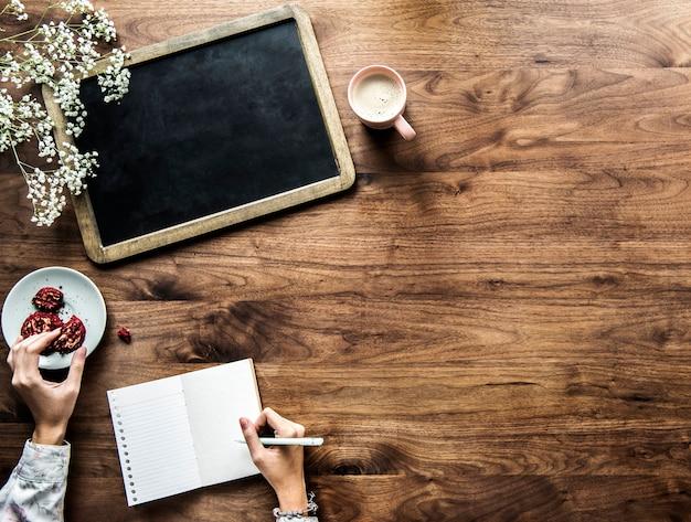 Vue aérienne du tableau noir vide et femme écrivant sur un journal vide avec espace copie Psd gratuit