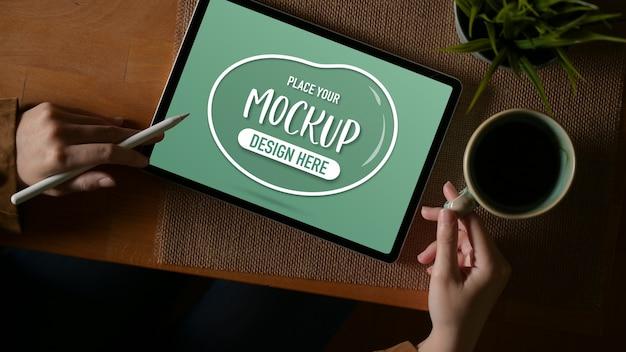 Vue Aérienne D'une Femme Travaillant Avec Une Maquette De Tablette Et Tenant Une Tasse De Café Sur Une Table En Bois PSD Premium
