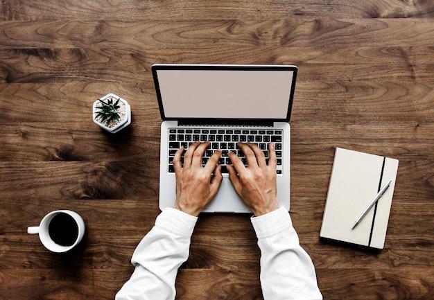 Vue Aérienne D'un Homme à L'aide D'ordinateur Portable Sur La Table En Bois Psd gratuit