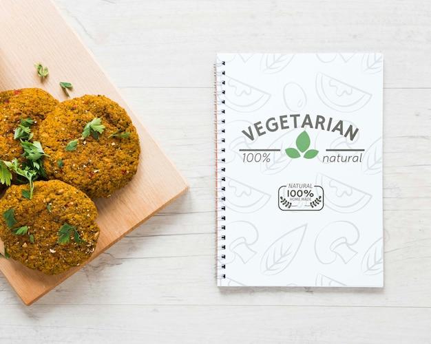 Vue de dessus arrangement avec nourriture végétarienne et cahier Psd gratuit