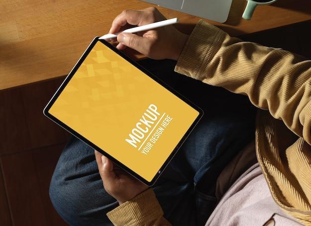 Vue De Dessus Des Mains Mâles à L'aide D'une Maquette De Tablette Numérique Alors Qu'il était Assis Sur Le Lieu De Travail PSD Premium