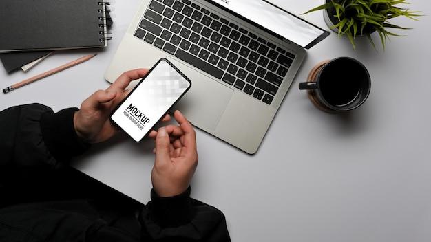 Vue De Dessus Des Mains Mâles à L'aide De Smartphone Tout En Travaillant Avec Une Maquette D'ordinateur Portable PSD Premium