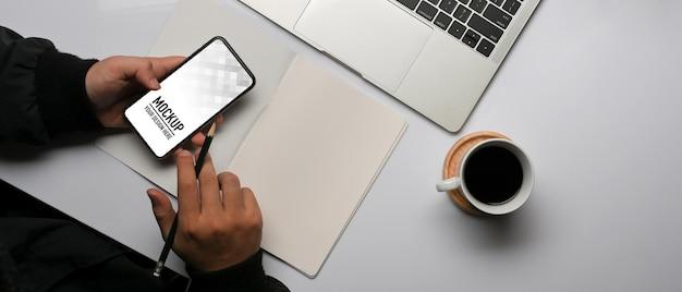 Vue De Dessus Des Mains Mâles Travaillant Avec Une Maquette De Smartphone PSD Premium