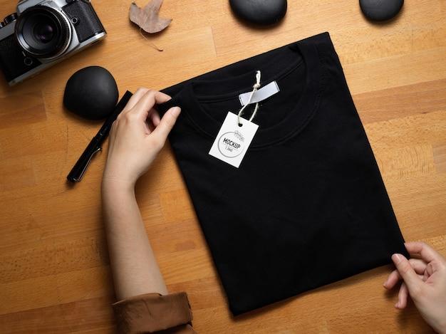 Vue De Dessus Des Mains Tenant Une Maquette De T-shirt Noir Avec étiquette De Prix Sur Un Bureau En Bois PSD Premium