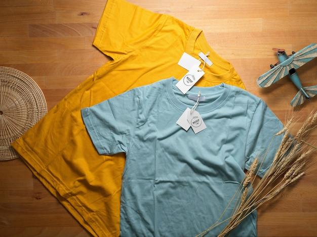 Vue De Dessus De La Maquette De T-shirt Jaune Et Bleu Avec Des étiquettes De Prix Maquette Sur Table En Bois PSD Premium