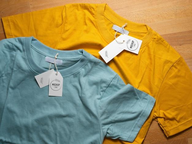 Vue De Dessus De La Maquette De T-shirts Jaunes Et Bleus Avec Des étiquettes De Prix Sur Table En Bois PSD Premium