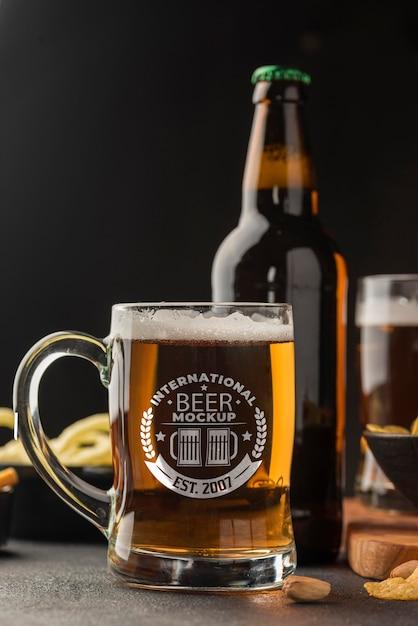 Vue De Face De La Bouteille De Bière Et Pinte Avec Assortiment De Collations Psd gratuit
