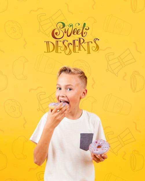 Vue De Face D'un Enfant Mangeant Un Beignet Psd gratuit