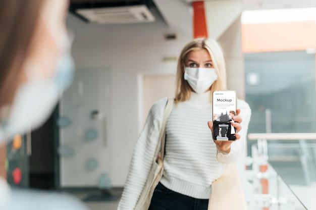 Vue De Face De La Femme Avec Un Masque Médical Tenant Le Téléphone PSD Premium