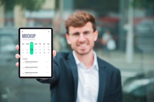 Vue De Face De L'homme D'affaires Souriant Tenant La Tablette Psd gratuit
