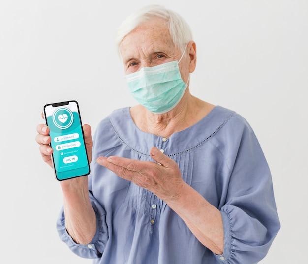 Vue Frontale, De, Femme Aînée, à, Masque Médical, Tenue, Smartphone Psd gratuit