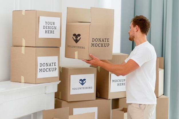 Vue Latérale Du Bénévole Masculin Avec Des Boîtes De Dons Psd gratuit