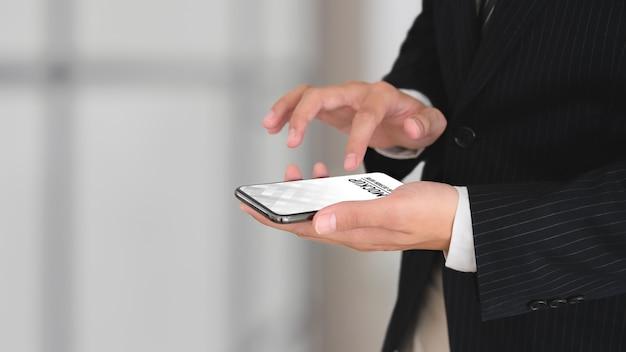 Vue Rapprochée De L'homme D'affaires En Costume Noir Mains à L'aide De La Maquette De Smartphone PSD Premium