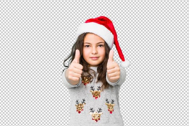 A menina que comemora o dia de natal com polegares levanta, felicidades sobre algo, apoia e respeita o conceito. Psd Premium
