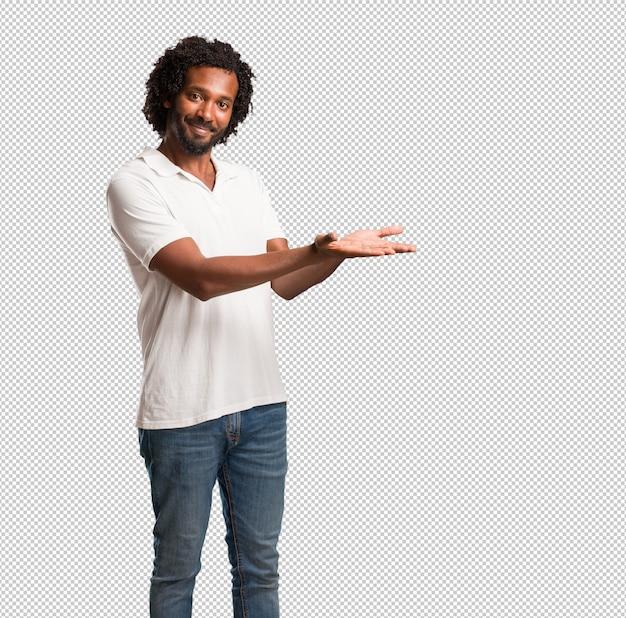 Afro-americano bonito segurando algo com as mãos, mostrando um produto, sorridente e alegre, oferecendo um objeto imaginário Psd Premium