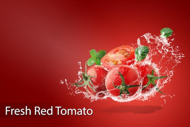 Água espirrando em tomates vermelhos frescos sobre fundo vermelho Psd Premium