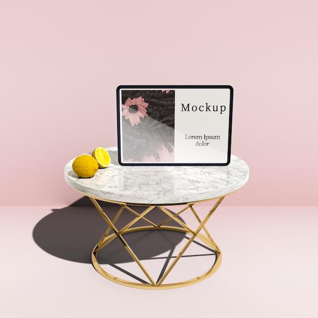 Alto ângulo de tablet na mesa com limões Psd grátis