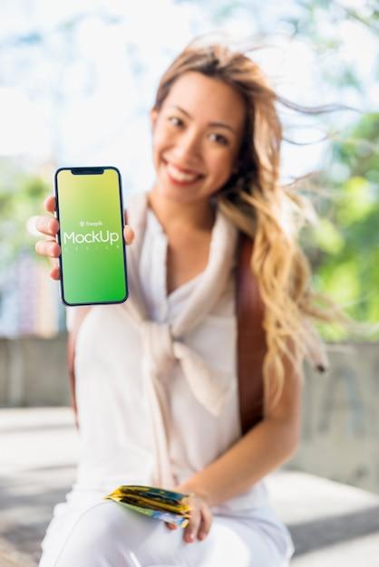 Amigável mulher apresentando smartphone maquete Psd grátis