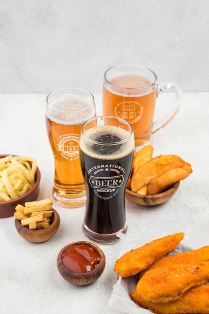 Ângulo alto de copos de cerveja com salgadinhos Psd Premium