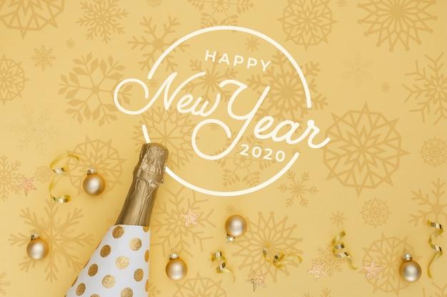 Ano novo 2020 com garrafa de ouro de champanhe e bolas de natal Psd grátis