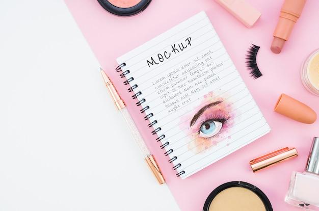 Arranjo de cosméticos de maquiagem com mock-up de bloco de notas Psd grátis