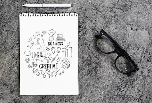 Arranjo plano leigo com caderno, óculos e caneta Psd grátis