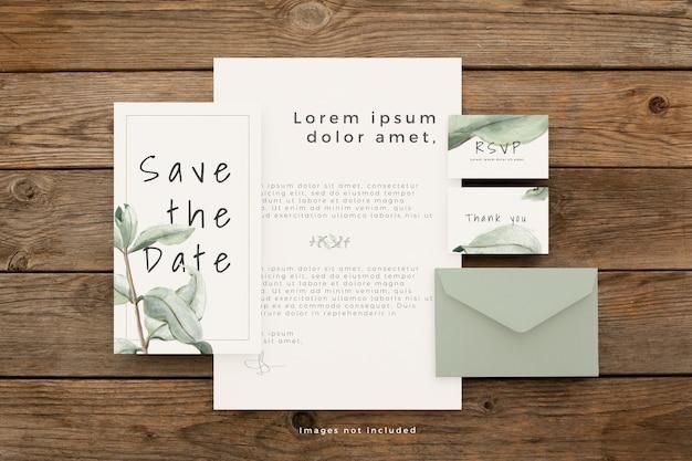 Artigos de papelaria de casamento com lindas folhas na mesa de madeira marrom Psd grátis