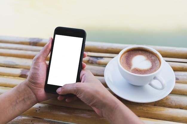 As mulheres mão segurando uma maquete do smartphone em uma mesa de bambu, café expresso quente, ao ar livre Psd Premium