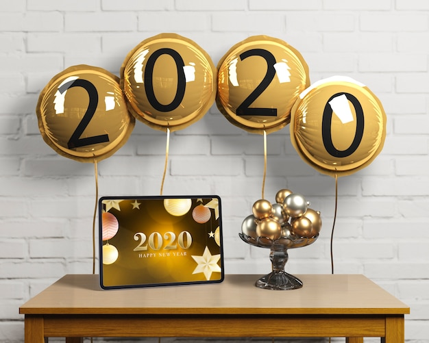 Balões com número de ano novo e tablet Psd grátis
