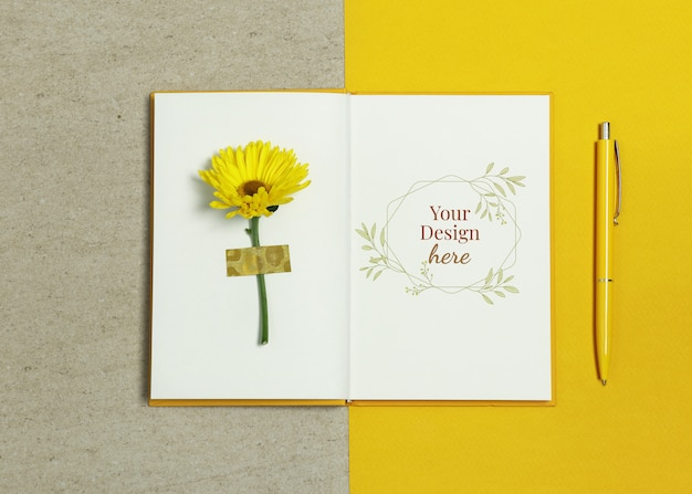 Caderno de maquete sobre fundo bege amarelo com caneta e flor de verão Psd Premium