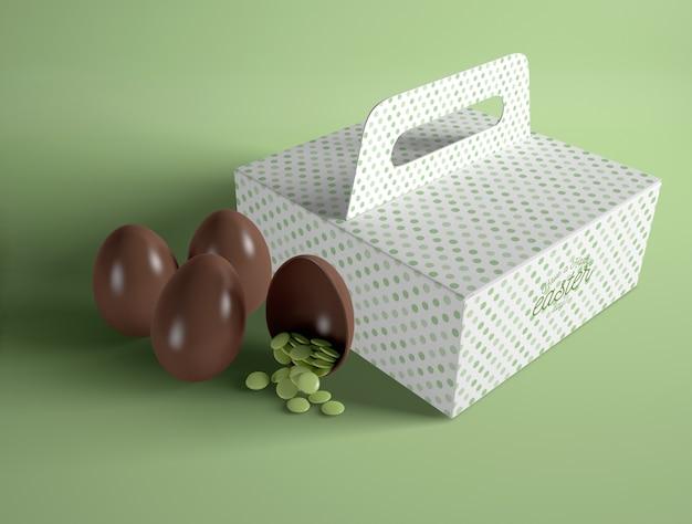 Caixa de alto ângulo com ovos de chocolate ao lado Psd grátis