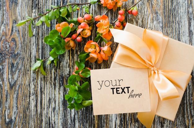 Caixa de presente com fita de laço, etiqueta em branco e delicado ramo de flores. Psd Premium