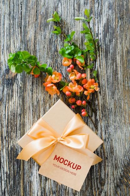 Caixa de presente com fita de laço, tag em branco e delicado ramo de flores. Psd Premium