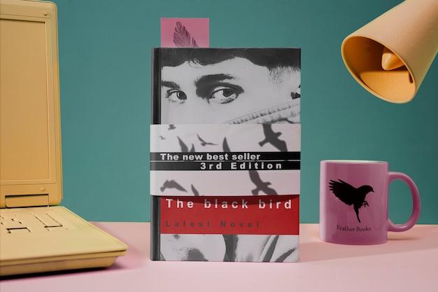 Capa da vista frontal de um livro e caneca Psd grátis