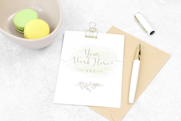 Cartão de convite de maquete com caneta e macarons Psd Premium