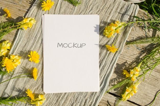 Cartão de maquete de artigos de papelaria de verão ou convite de casamento com flores amarelas em um espaço de madeira velho em estilo rústico e natural Psd Premium